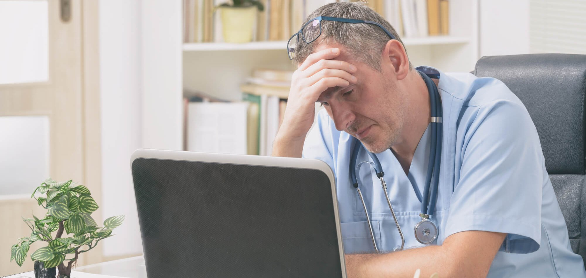 Doctor at Computer with Hand on Head