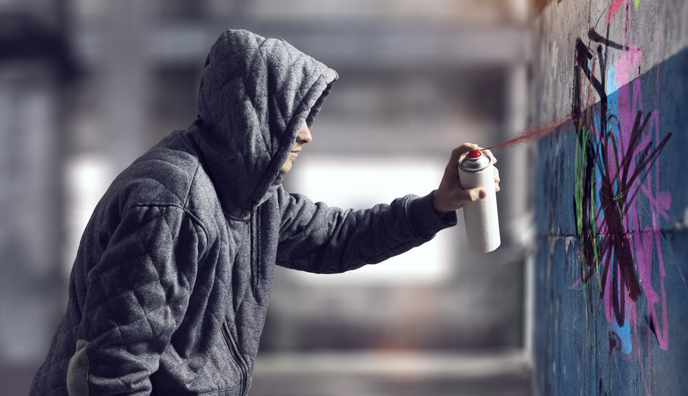 Hooded Person Graffiti Tagging a Wall