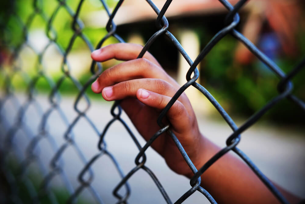 Hand on Chain Link Fence